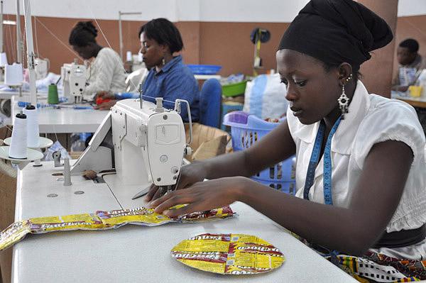 Eine Frau näht eine Tasche aus gebrauchten Glace-Beuteln.